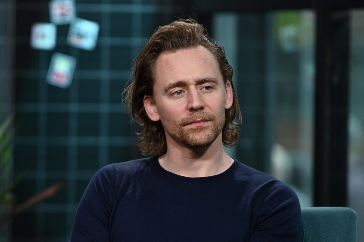Tom Hiddleston wearing a dark blue shirt and sitting in front of a blue wall