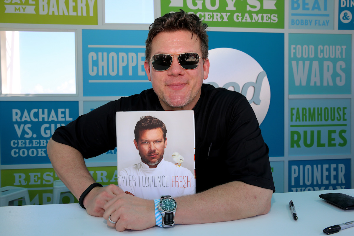 Tyler Florence poses with a copy of his cookbook at the 2014 Food Network South Beach Wine and Food Festival
