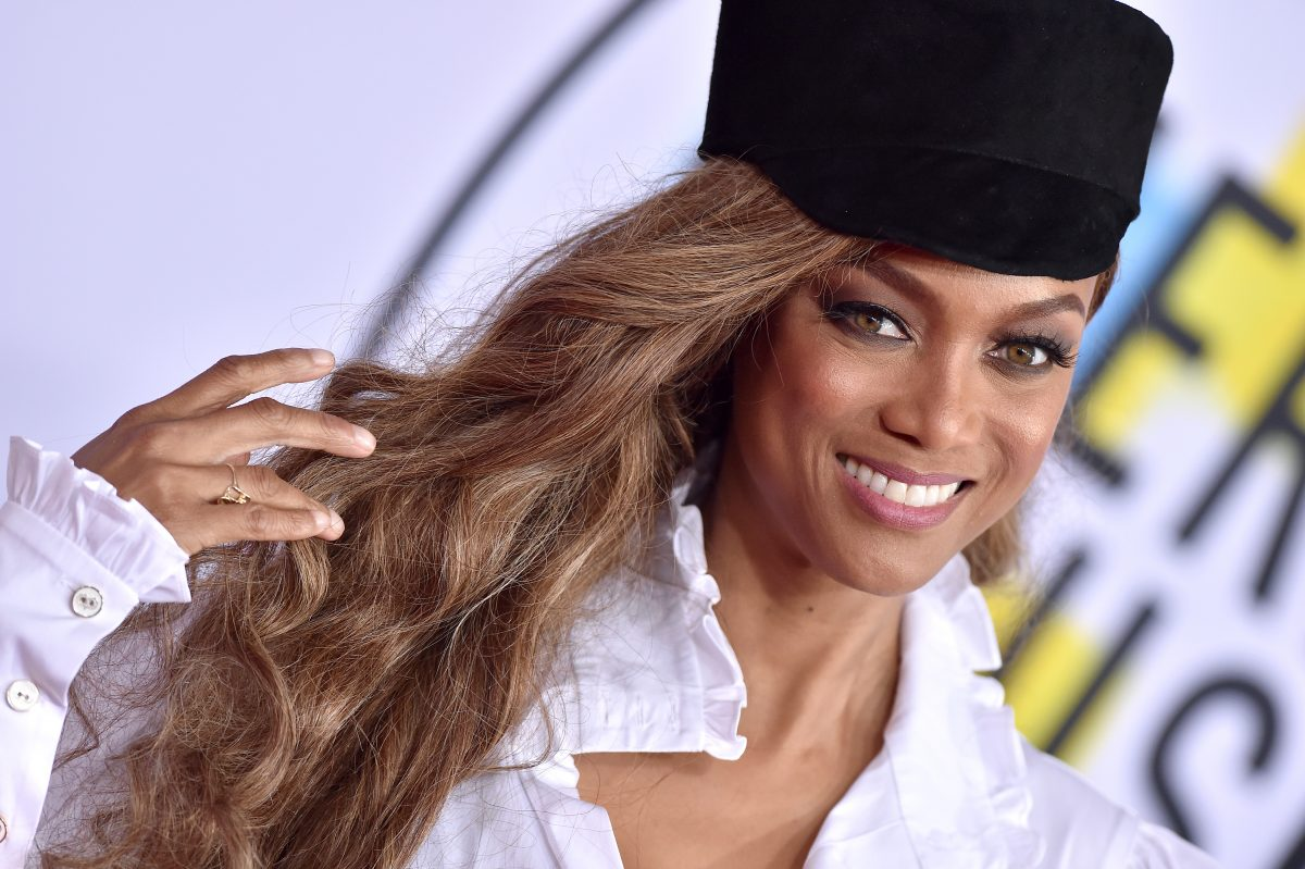 Tyra Banks smiling at the camera while wearing a white shirt and black hat.