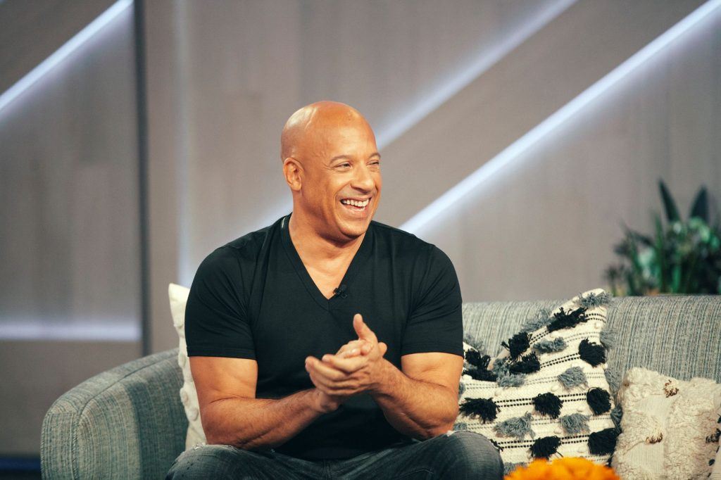 Vin Diesel sitting on a couch on the set of a talk show
