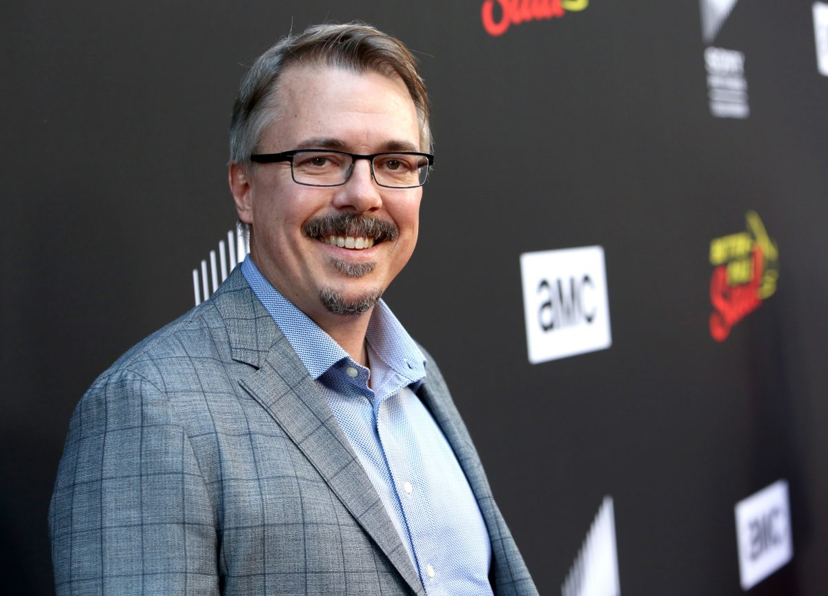 Breaking Bad and Better Call Saul creator Vince Gilligan wearing a blue button-up shirt and dark suit and standing in front of a black wall with 'AMC' written on it