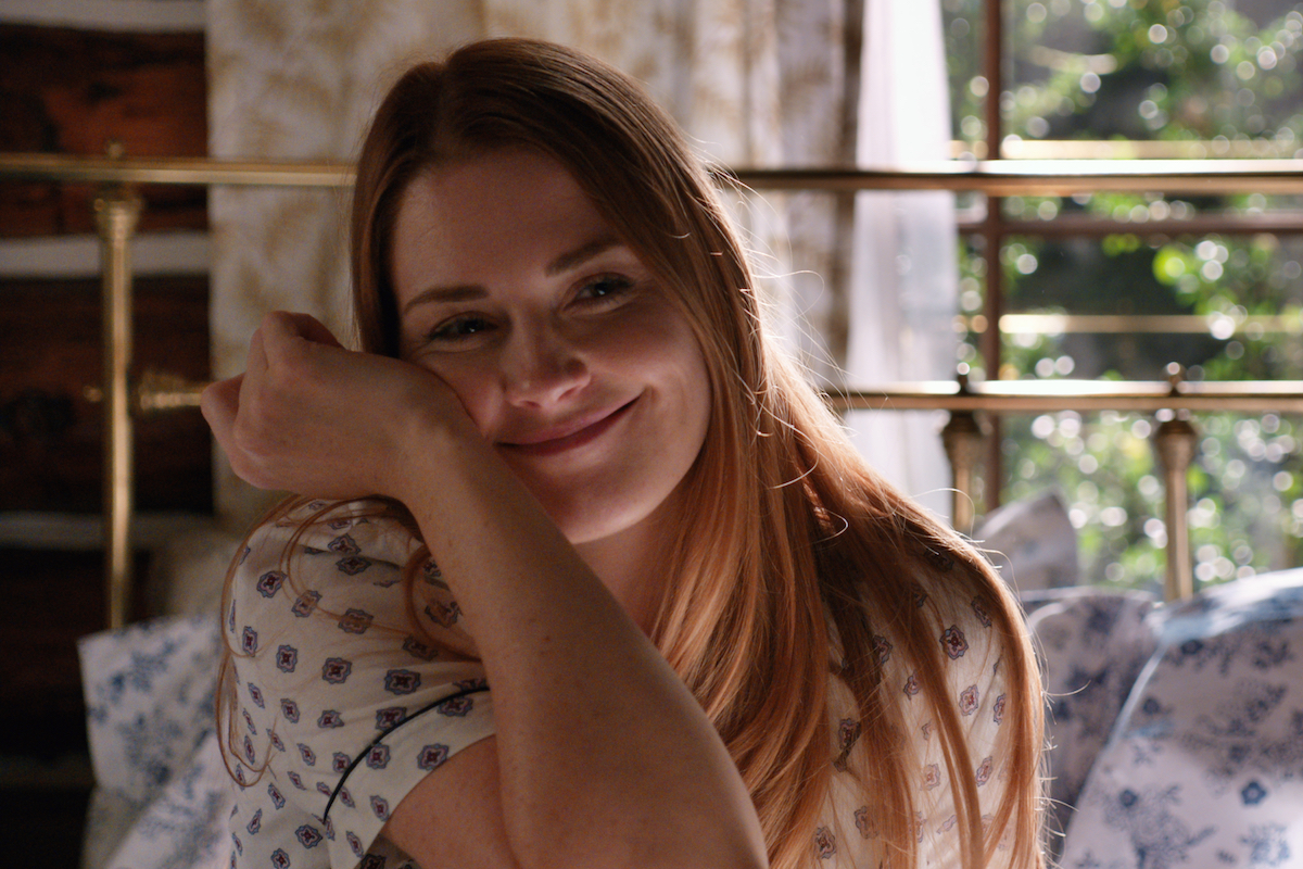 Smiling Mel (Alexandra Breckenridge) leaning cheek against her hand in 'Virgin River' Season 3