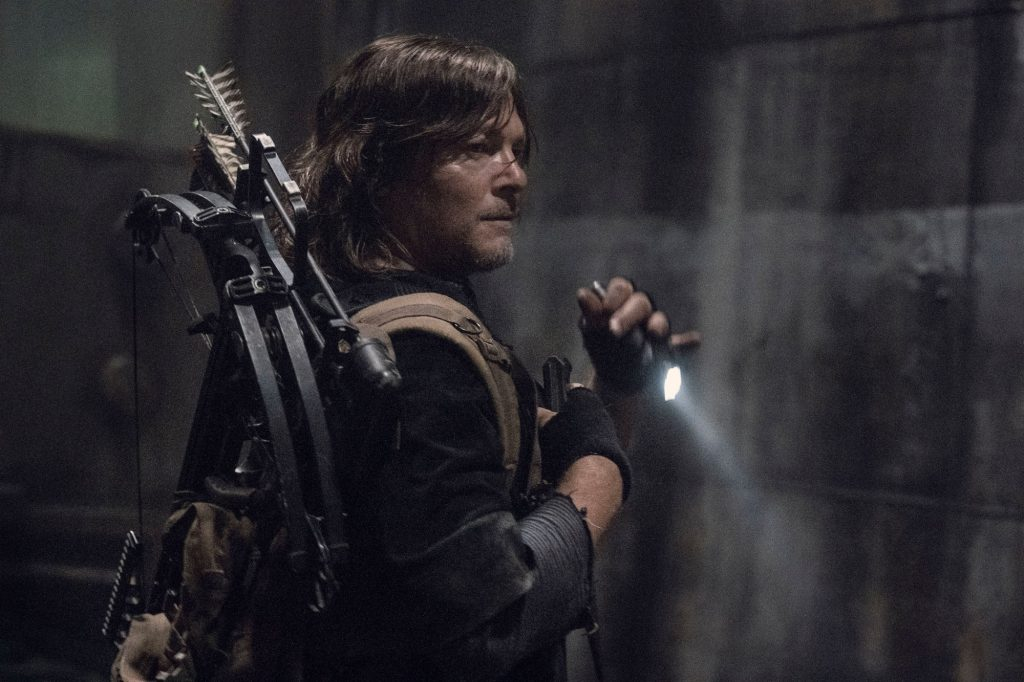 Norman Reedus in the final season of 'The Walking Dead' is standing in the dark, holding a knife, and looking over his shoulder