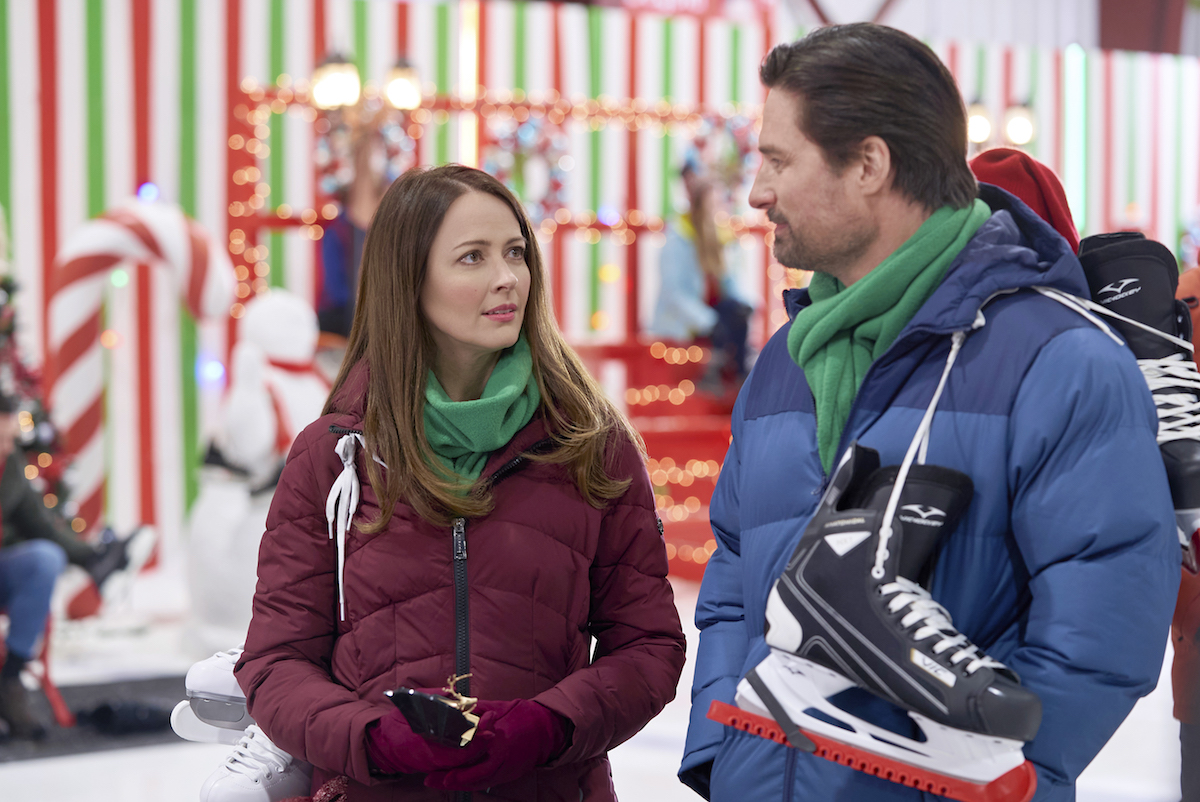 Amy Acker looking at Warren Christie, with ice skates on his shoulder, in 'Crashing Through the Snow'
