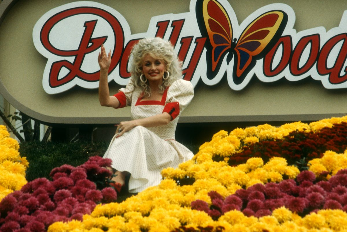 Dolly Parton in front of a Dollywood sign with red and yellow flowers surrounding her