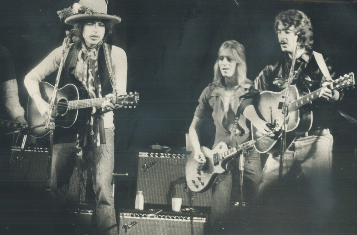 Bob Dylan and other musicians perform on stage in 1975.