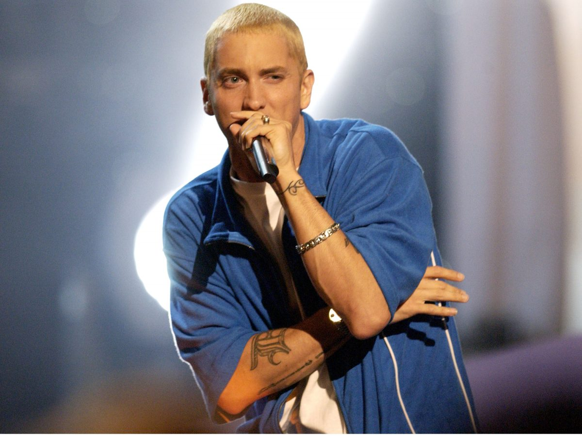 Eminem wearing a blue jacket and holding a microphone