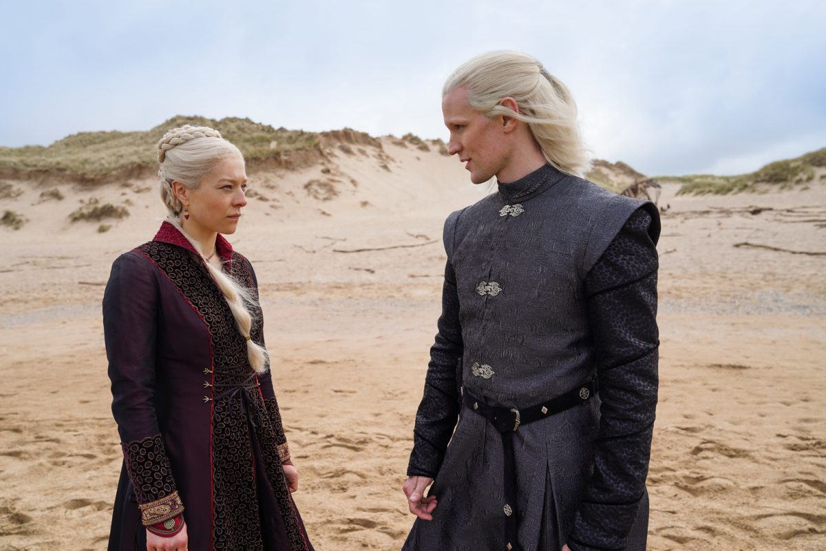 Emma D'Arcy and Matt Smith wearing blonde wigs and standing in a desert landscape in HBO's 'House of the Dragon'