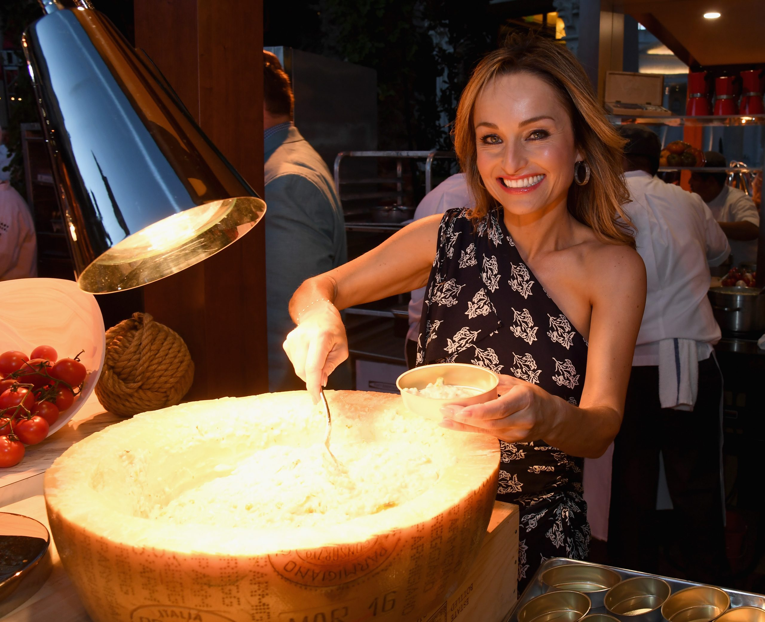 Food Network star Giada De Laurentiis prepares a meal at her Las Vegas restaurant, Giada, in 2018 wearing an off-the-shoulder print top.
