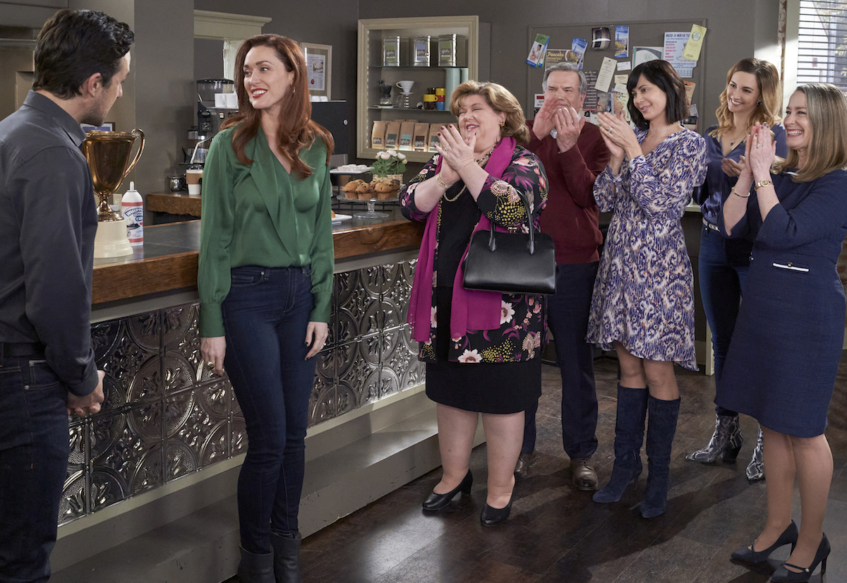 Abigail in a green shirt and jeans standing next to other cast members in episode of 'Good Witch'