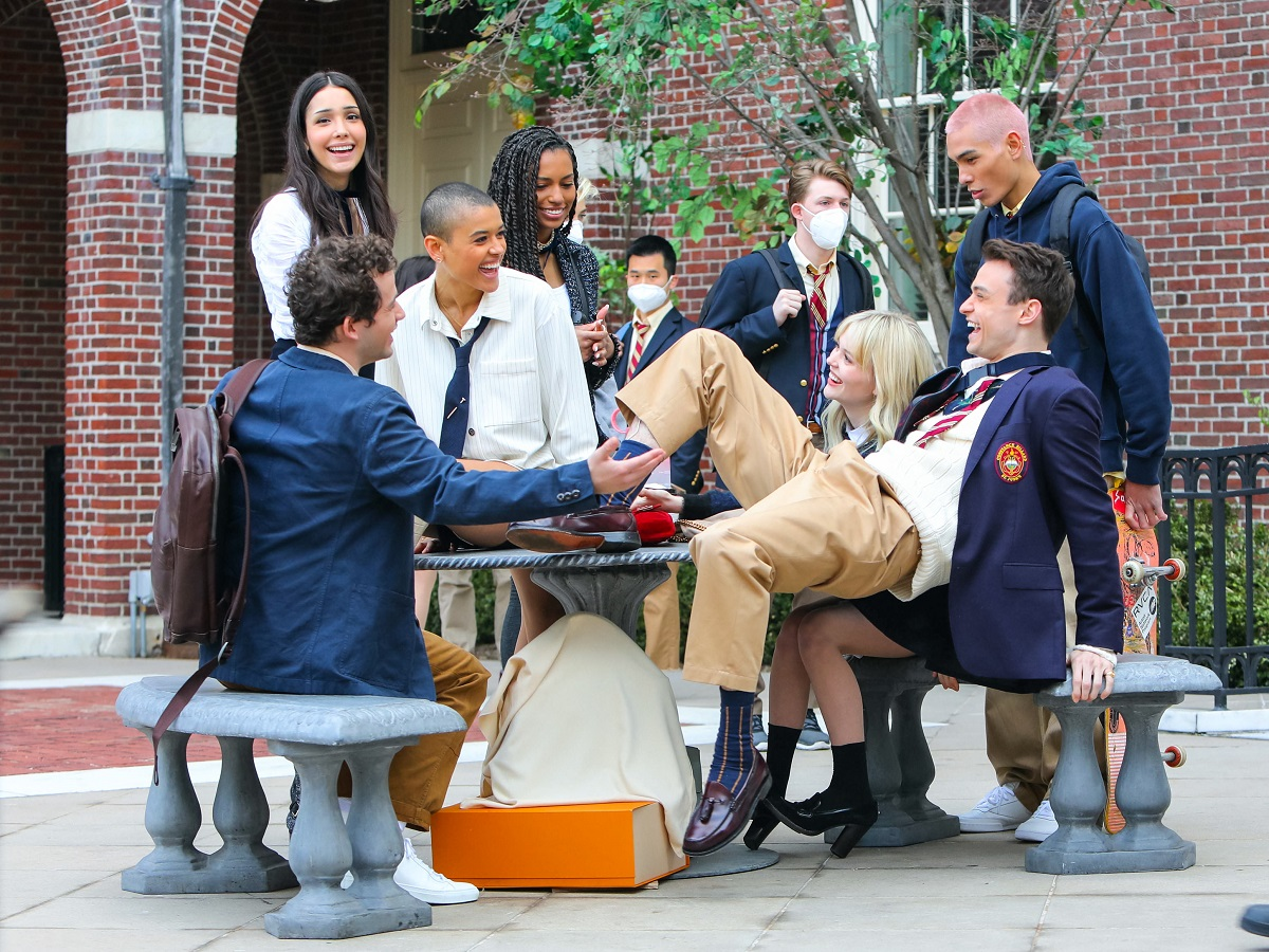 The 'Gossip Girl' main cast on set sitting at a table, as extras wear masks behind them.