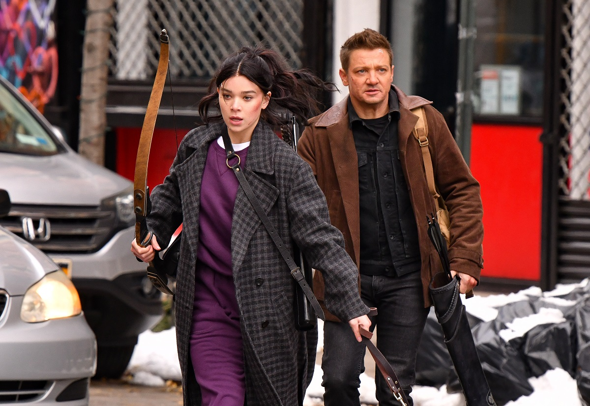 Hailee Steinfeld (L) and Jeremy Renner seen on the set of 'Hawkeye' with Steinfeld holding a bow and a dog leash