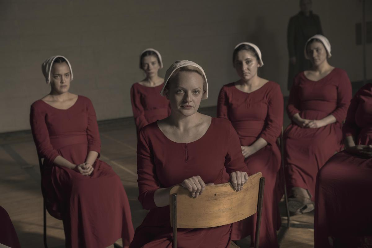Brianna (Bahia Watson) and June (Elisabeth Moss) in 'The Handmaid's Tale' Season 3. Five women sit in school desk chairs in an old gymnasium. They wear red Handmaid dresses and white bonnets.