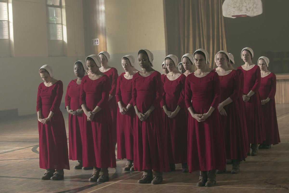 Janine (Madeline Brewer), Brianna (Bahia Watson), Ofmatthew (Ashleigh LaThrop), Alma (Nina Kiri), and June (Elisabeth Moss) in 'The Handmaid's Tale' Season 3. A group of about 20 women dressed in red Handmaid dresses and white bonnets stand in five lines with their feet together and hands crossed in front of them. They stand in an old school gymnasium.