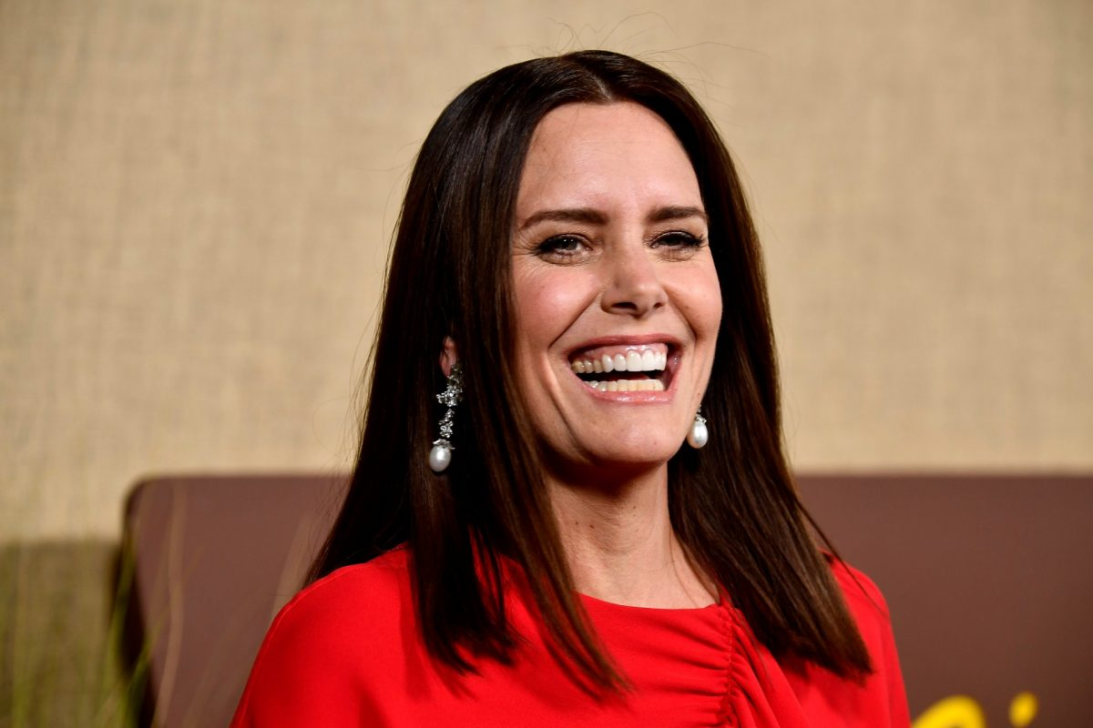 ione skye smiles while wearing a red outfit