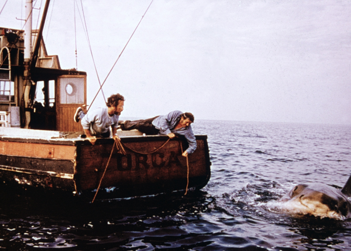 Richard Dreyfuss and Robert Shaw leaning off the back of their boat, 'Orca in a still from the film, 'Jaws,' 1975