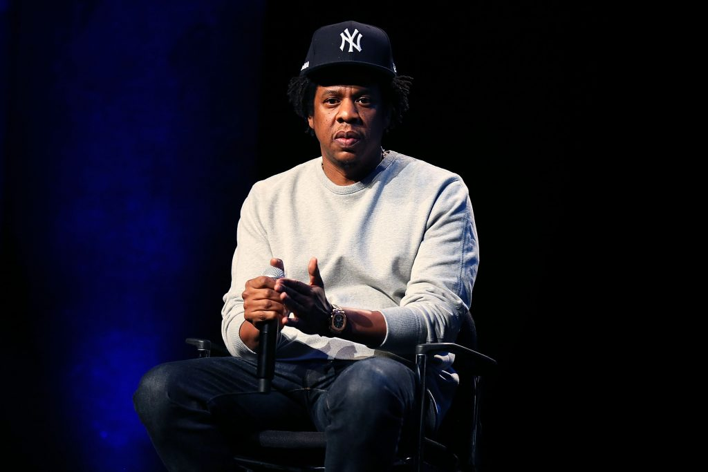Jay-Z sits on stage wearing a Yankees hat