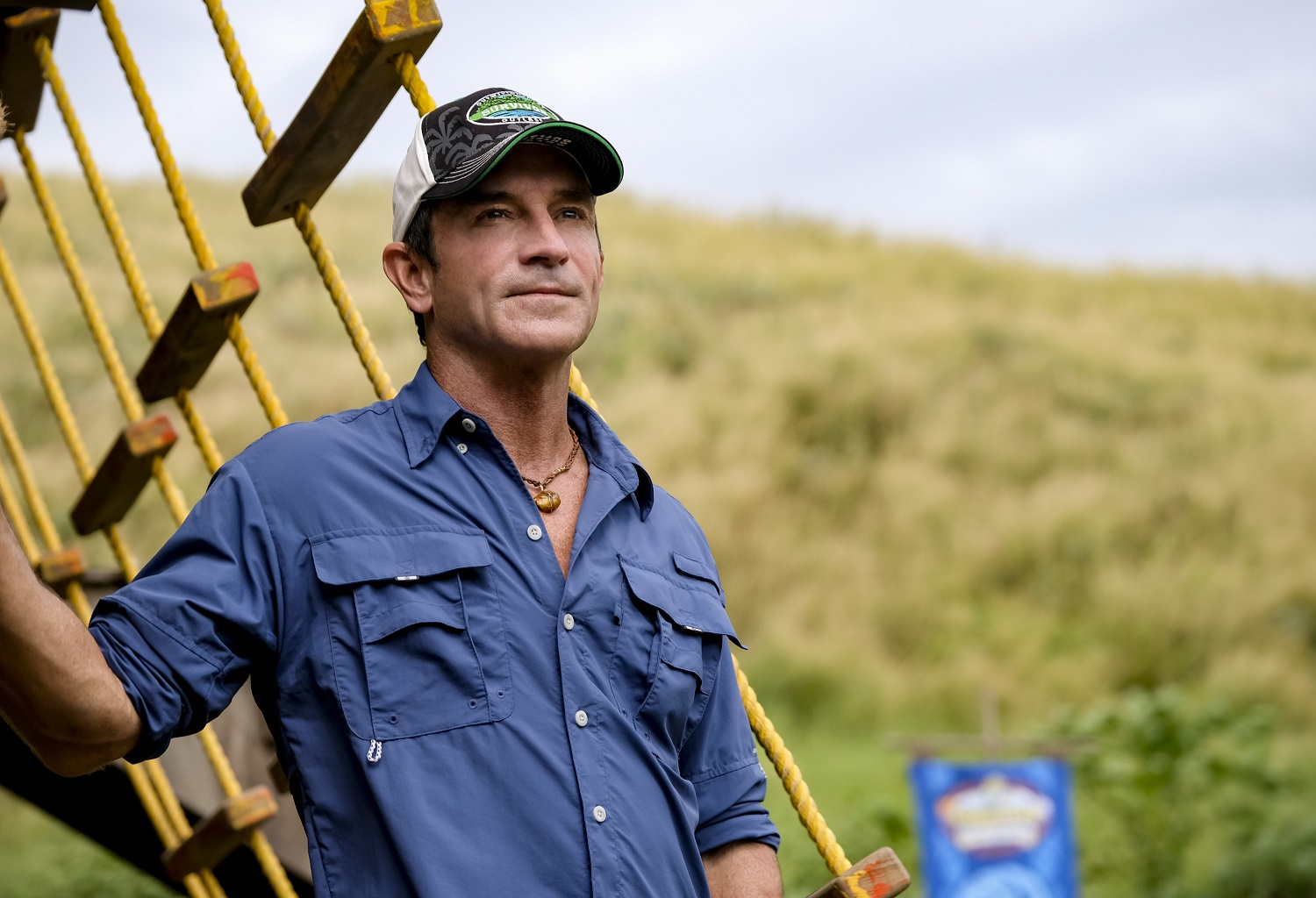 Jeff Probst, host of Survivor 41 wearing a blue button down, standing on a boat, looking into the distance