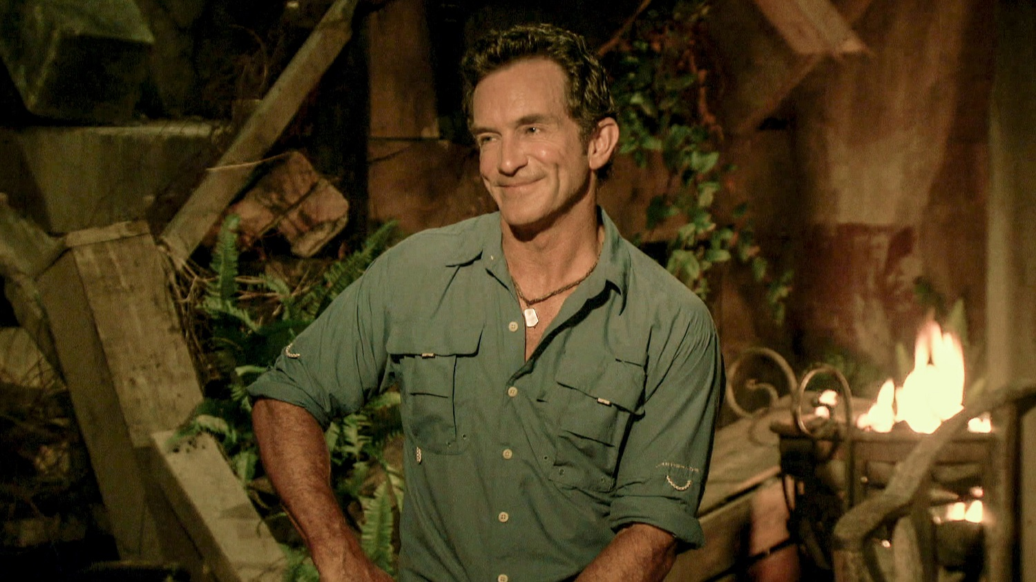 Jeff Probst, host of 'Survivor 41' sits and smiles during tribal council
