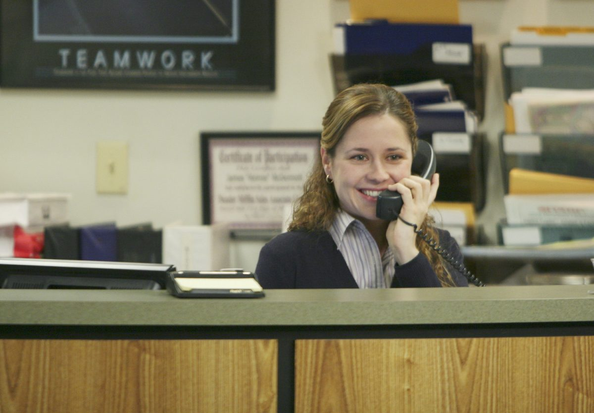 The Office star Jenna Fischer as her character Pam, smiling at the reception desk at Dunder Mifflin