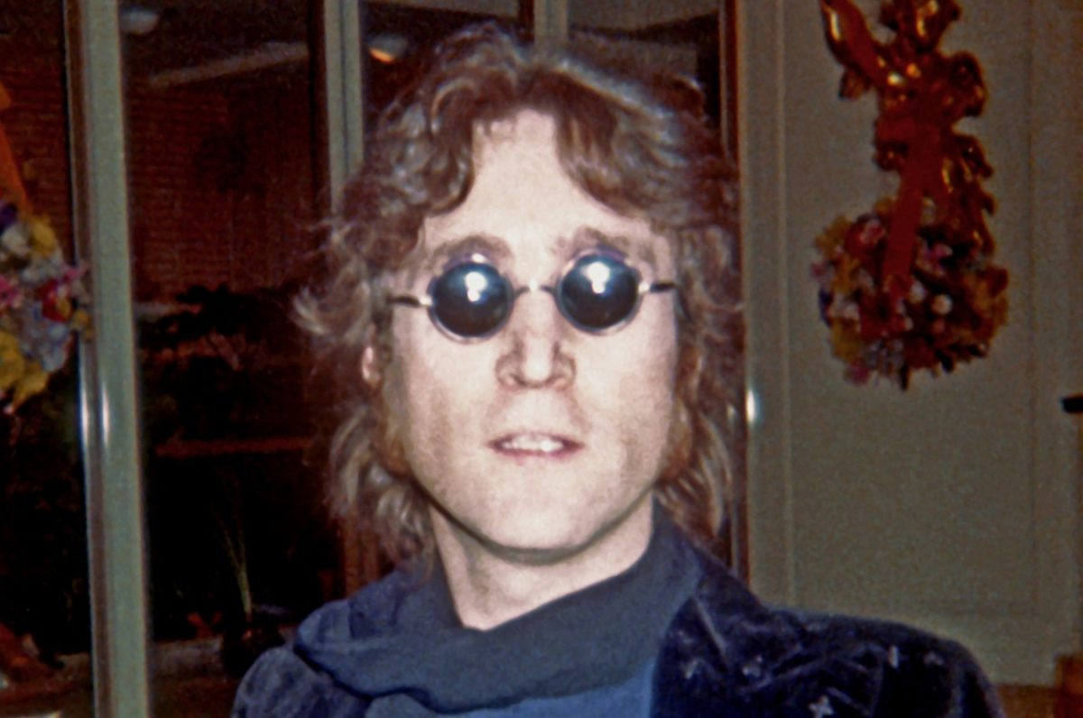 John Lennon, wearing sunglasses, stares at the camera in 1974.