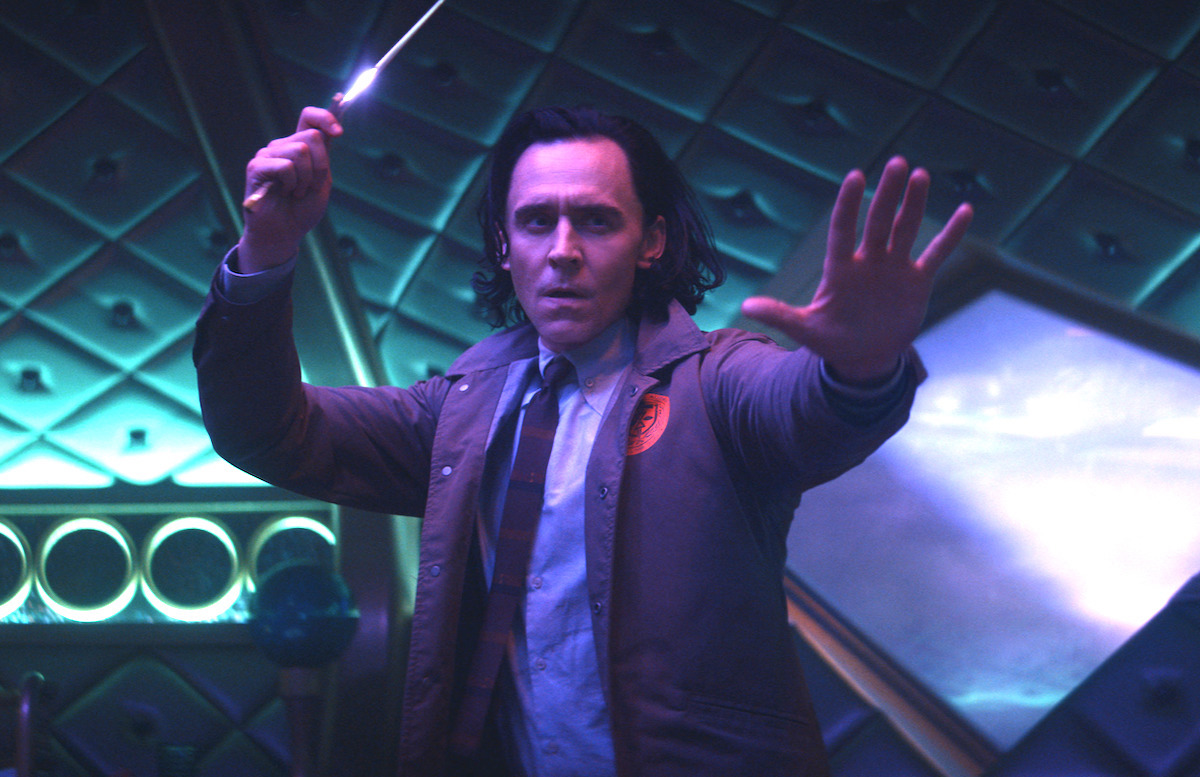 Tom Hiddleston wields a dagger while wearing a shirt and tie with a brown TVA jacket in a room lit with purple and teal lighting.