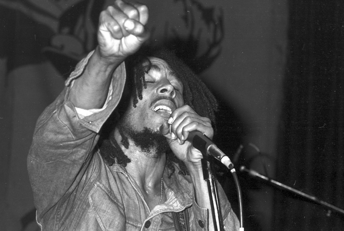 Bob Marley sings, eyes closed, fist raised, while holding a microphone in 1975.