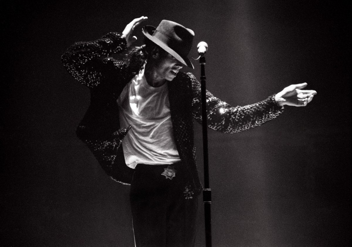 Michael Jackson wearing a fedora and a sparkly jacket while doing the moonwalk in front of a microphone