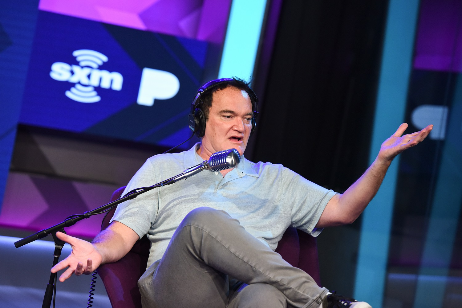 Quentin Tarantino sits in a chair and speaks into a microphone during an interview.