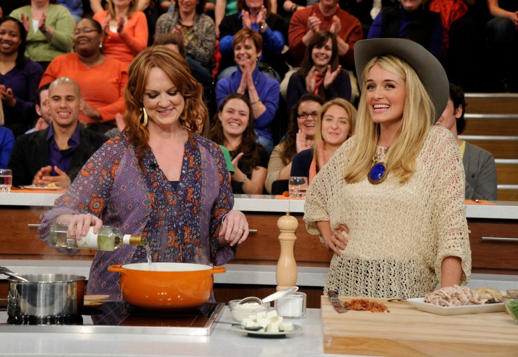 Ree Drummond stirs a meal in an orange pot while talking with Daphne Oz on 'The Chew' television show.