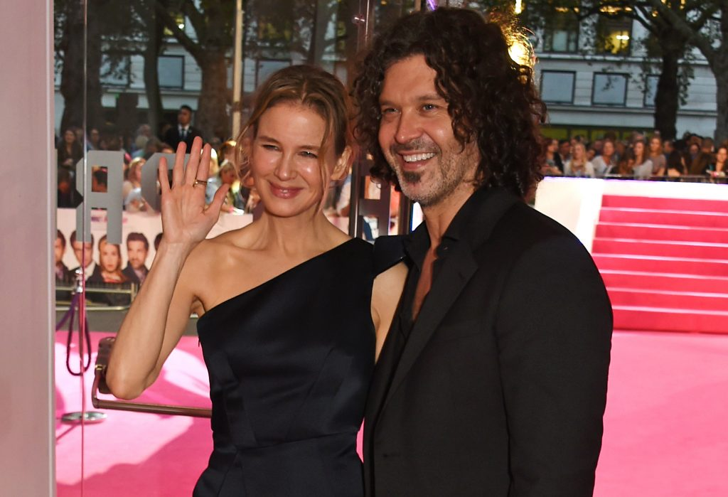Renee Zellweger waves at the camera while standing next to Doyle Bramhall