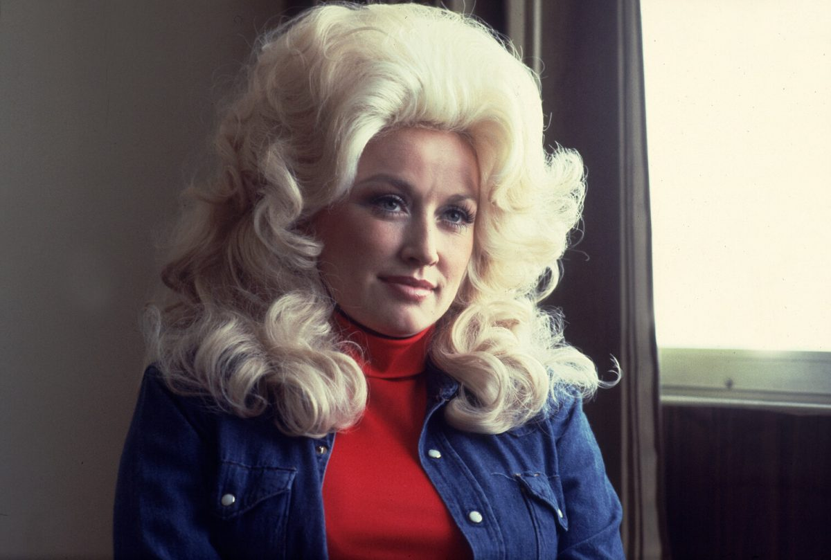 Portrait of Dolly Parton at the Holiday Inn in Chicago, Illinois, April 30, 1977. She's wearing her hair big and blonde. She has a red top on and a jean jacket.