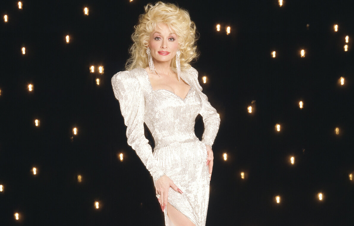 Dolly Parton in a tight white and silver dress in a promotion for 'The Dolly Show.' She's standing in front of a black, starry background.