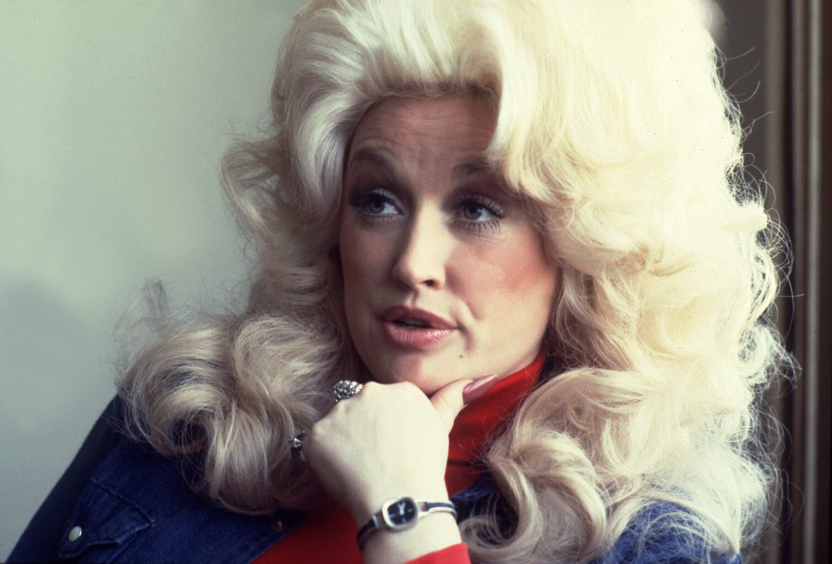 A close-up of Dolly Parton as she speaks in 1977. Her hair is big, blonde, and curly, she's wearing a red turtleneck and a jean jacket.