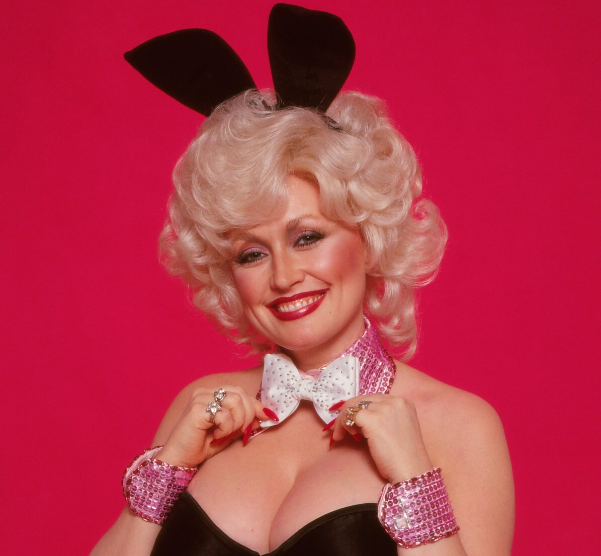 Dolly Parton's photo for Playboy Magazine in 1978. She's in the iconic bunny costume with black bunny ears and a silver bow around her neck.