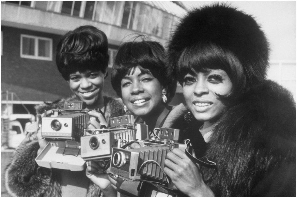 Diana Ross and the Supremes smiling and holding cameras in London.