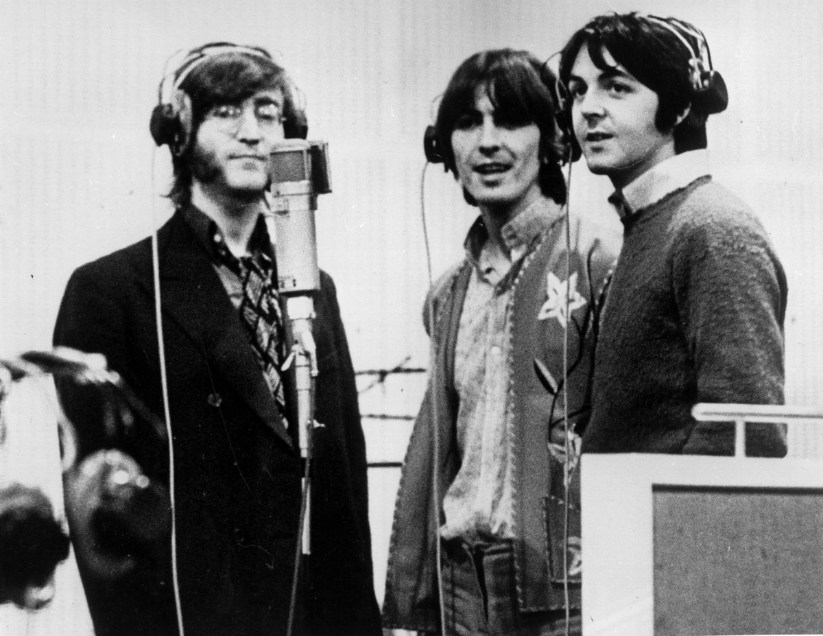 The Beatles' John Lennon, George Harrison, and Paul McCartney standing around a microphone
