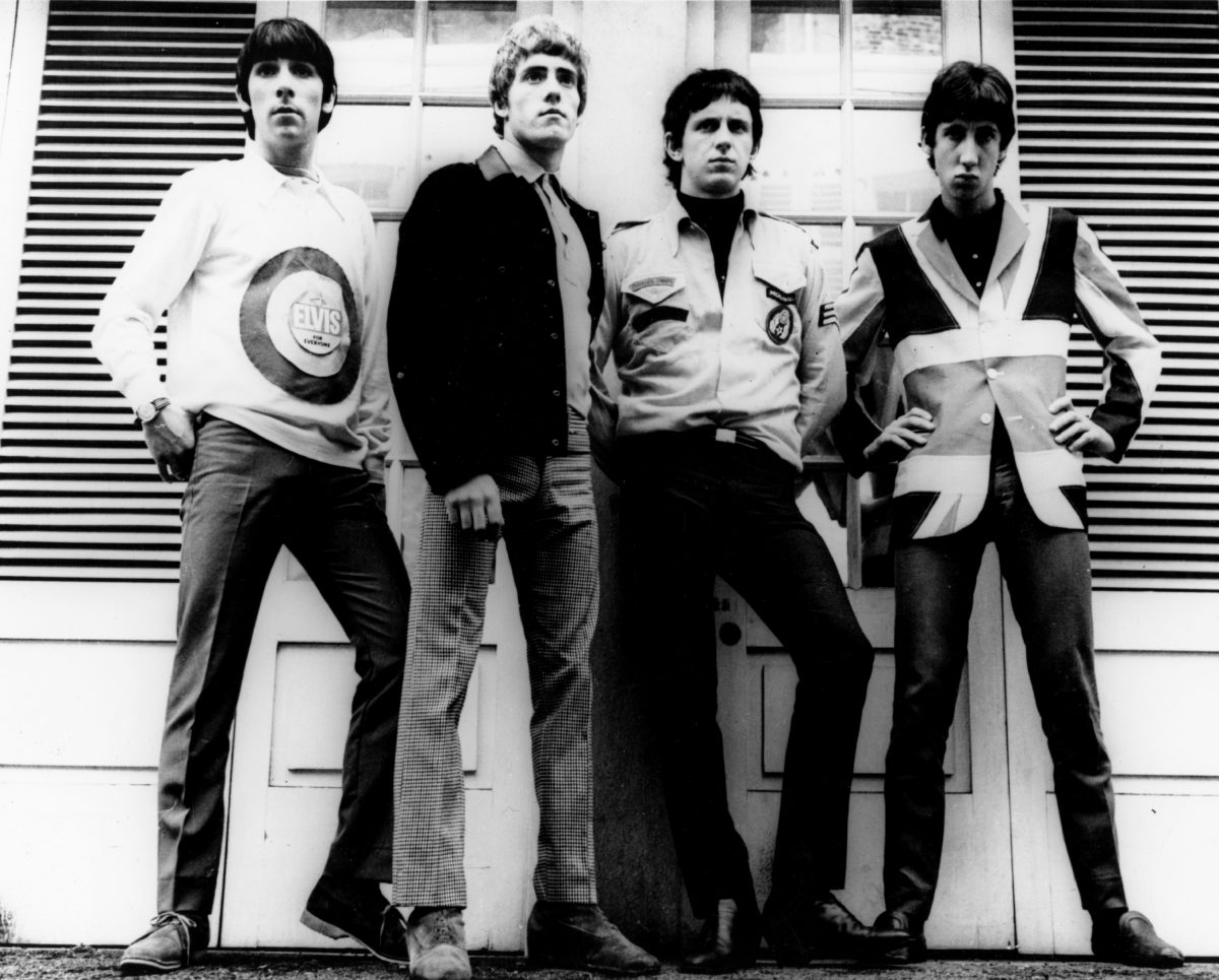 Keith Moon, Roger Daltrey, John Entwistle, and Pete Townshend of The Who standing in front of a wall