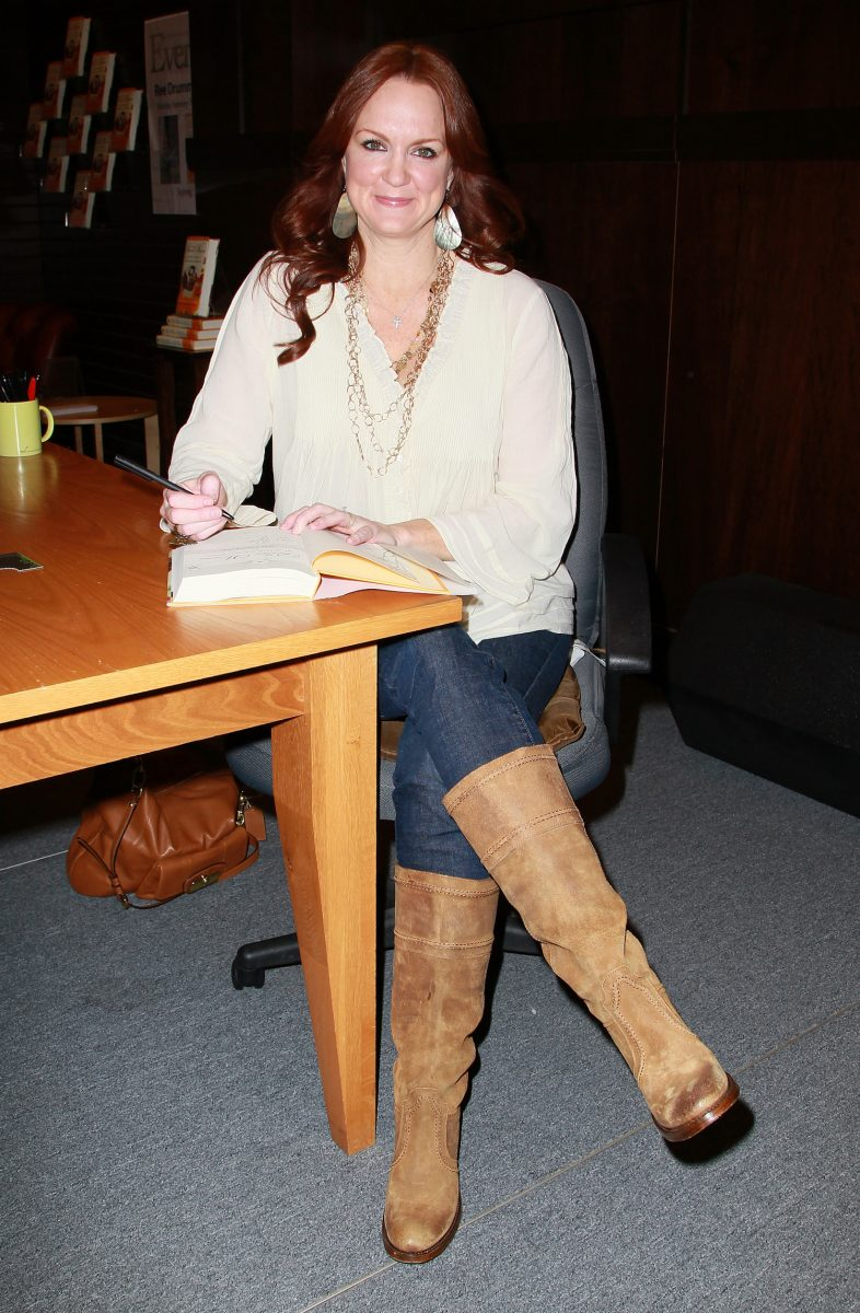 Ree Drummond smiling while sitting down and signing a book in 2011