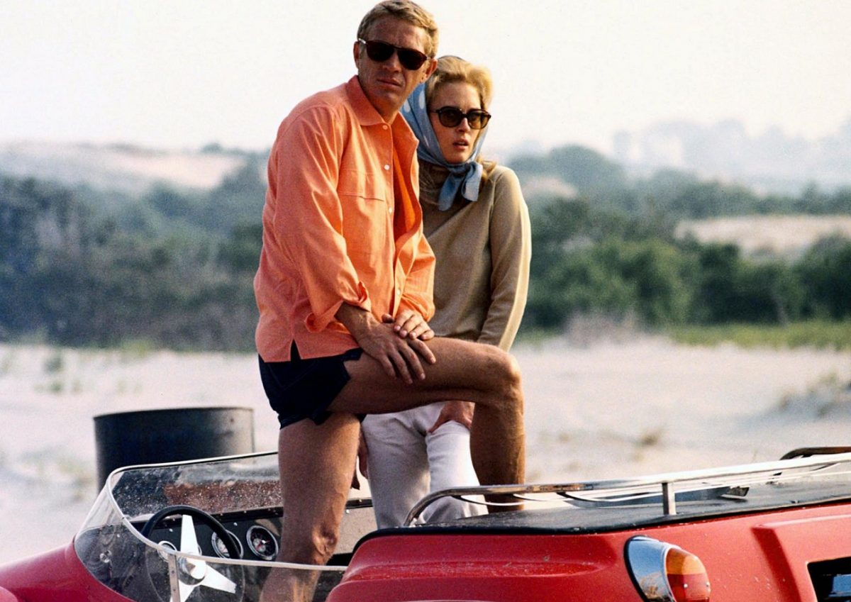 Steve McQueen and Faye Dunaway posing in an open-top car in a publicity image issued for the film, 'The Thomas Crown Affair.'