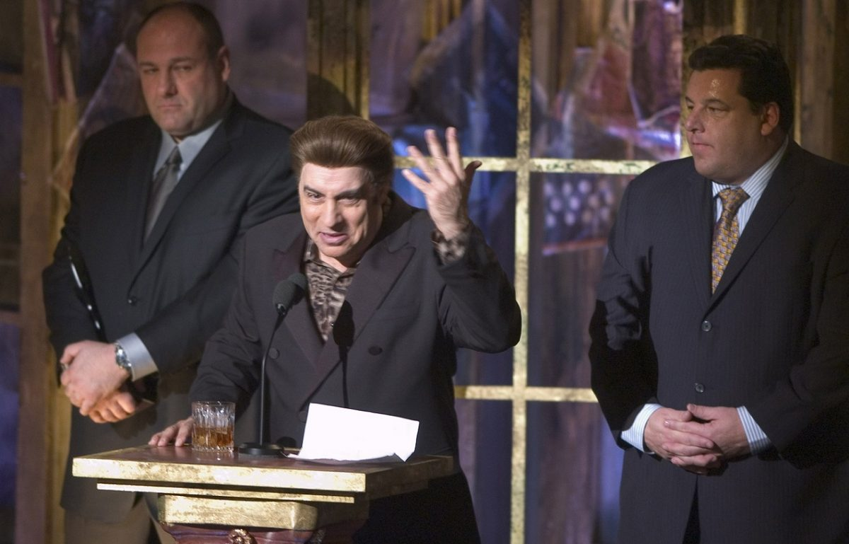 Steven Van Zandt in character as Silvio Dante speaks during the Rock and Roll Hall of Fame Induction Ceremony in 2005. James Gandolfini and Steve Schirripa stand behind him.