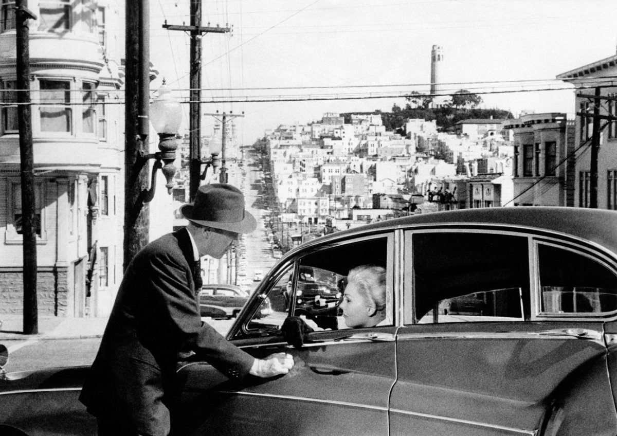 Jimmy Stewart leans on a car in which Kim Novak sits in the driver's seat with a view of San Francisco in the background. From 'Vertigo'