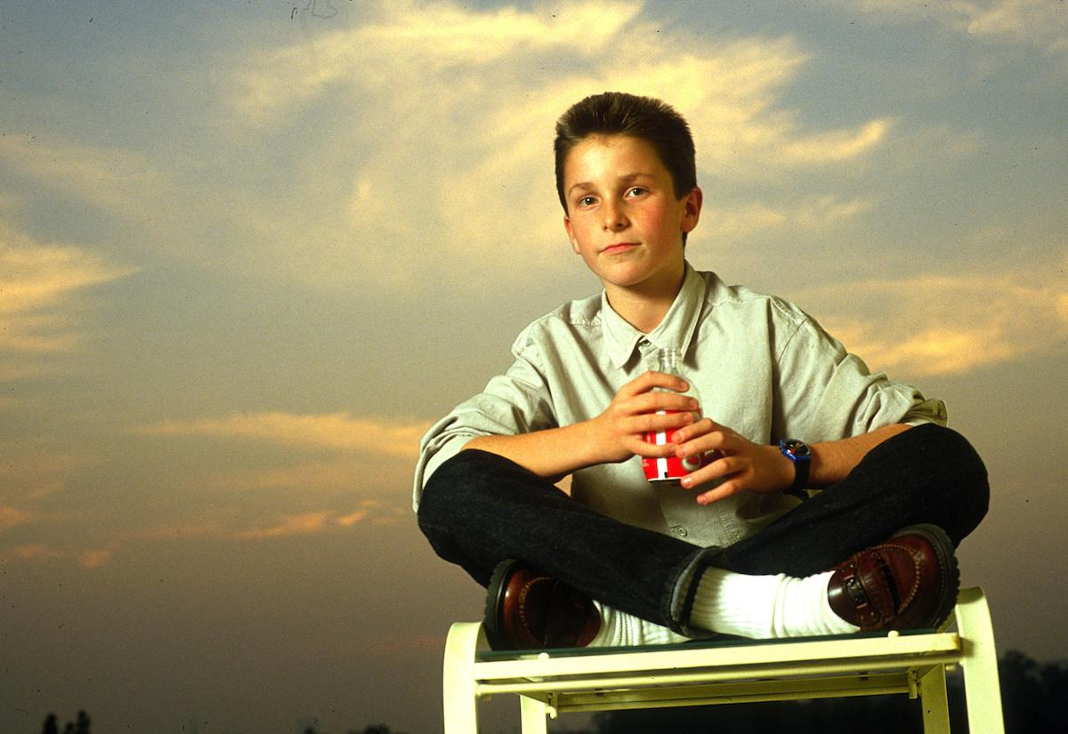 13-year-old Christian Bale poses on a chair to promote 'Empire of the Sun'