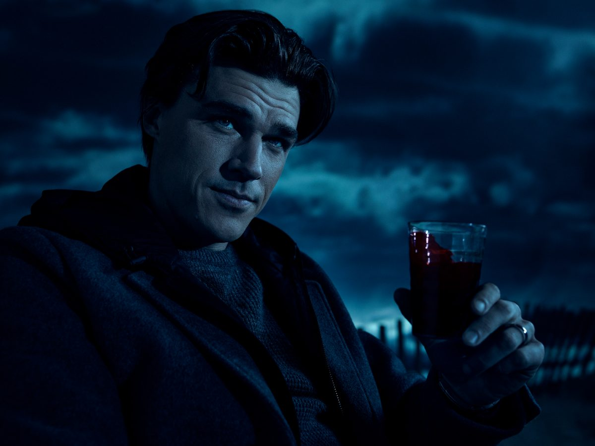 'American Horror Story' Season 10 image shows Finn Wittrock wearing a dark sweater and coat and holding a cup of blood. He looks like he's lounging and a cloudy sky is behind him. New episodes come out every Wednesday.