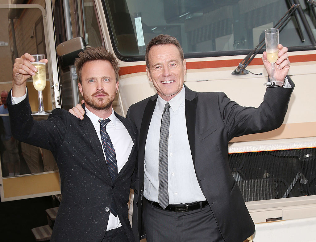Aaron Paul and Bryan Cranston hold champagne toast glasses as they stand in front of the 'Breaking Bad' RV during a press event. Each are wearing a dark suit and tie with white shirts underneath and big smiles all-around.