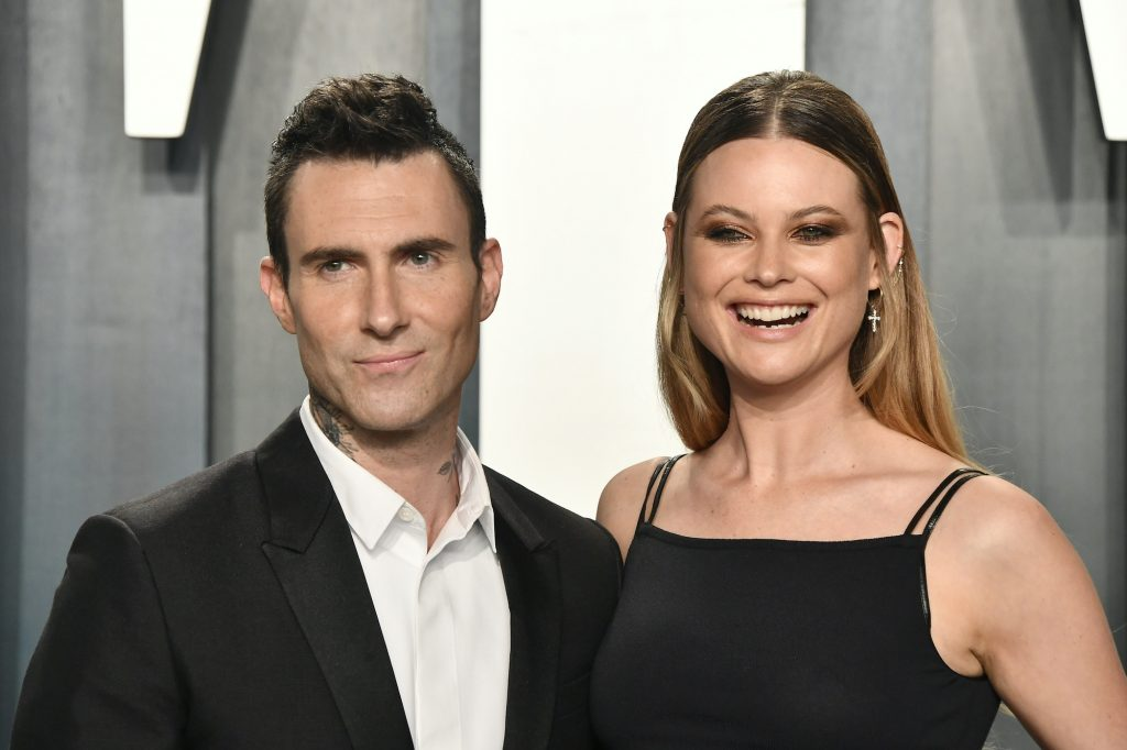 Adam Levine and Behati Prinsloo smiling in front of a blue background