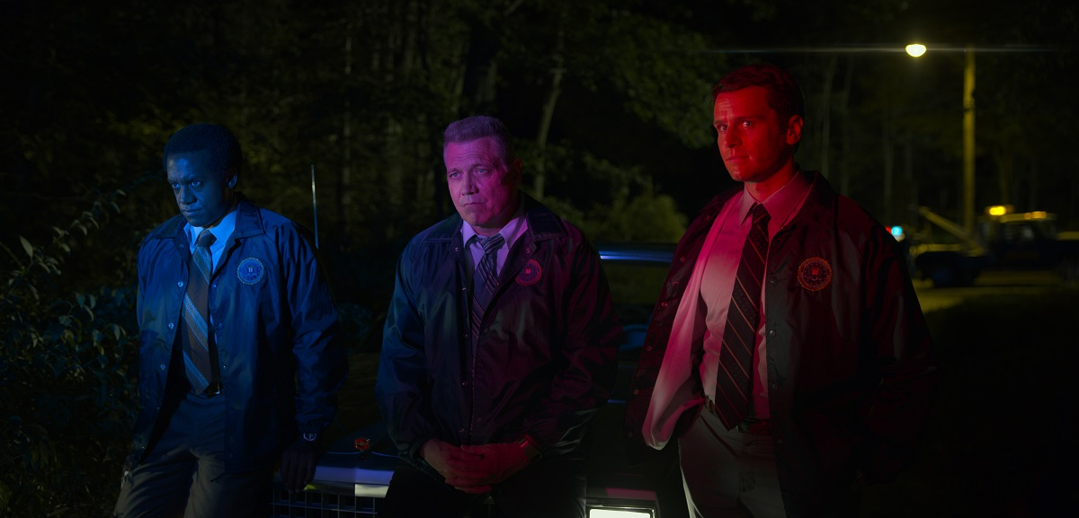 Albert Jones, Holt McCallany, and Jonathan Groff are lit by red and blue police lights in 'Mindhunter.'