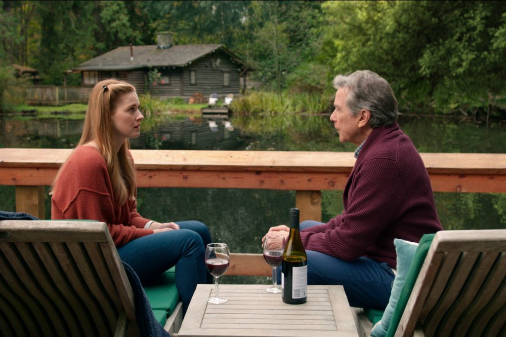 Alexandra Breckenridge as Mel Monroe and Tim Matheson as Doc Mullins sitting on a doc chatting in 'Virgin River'