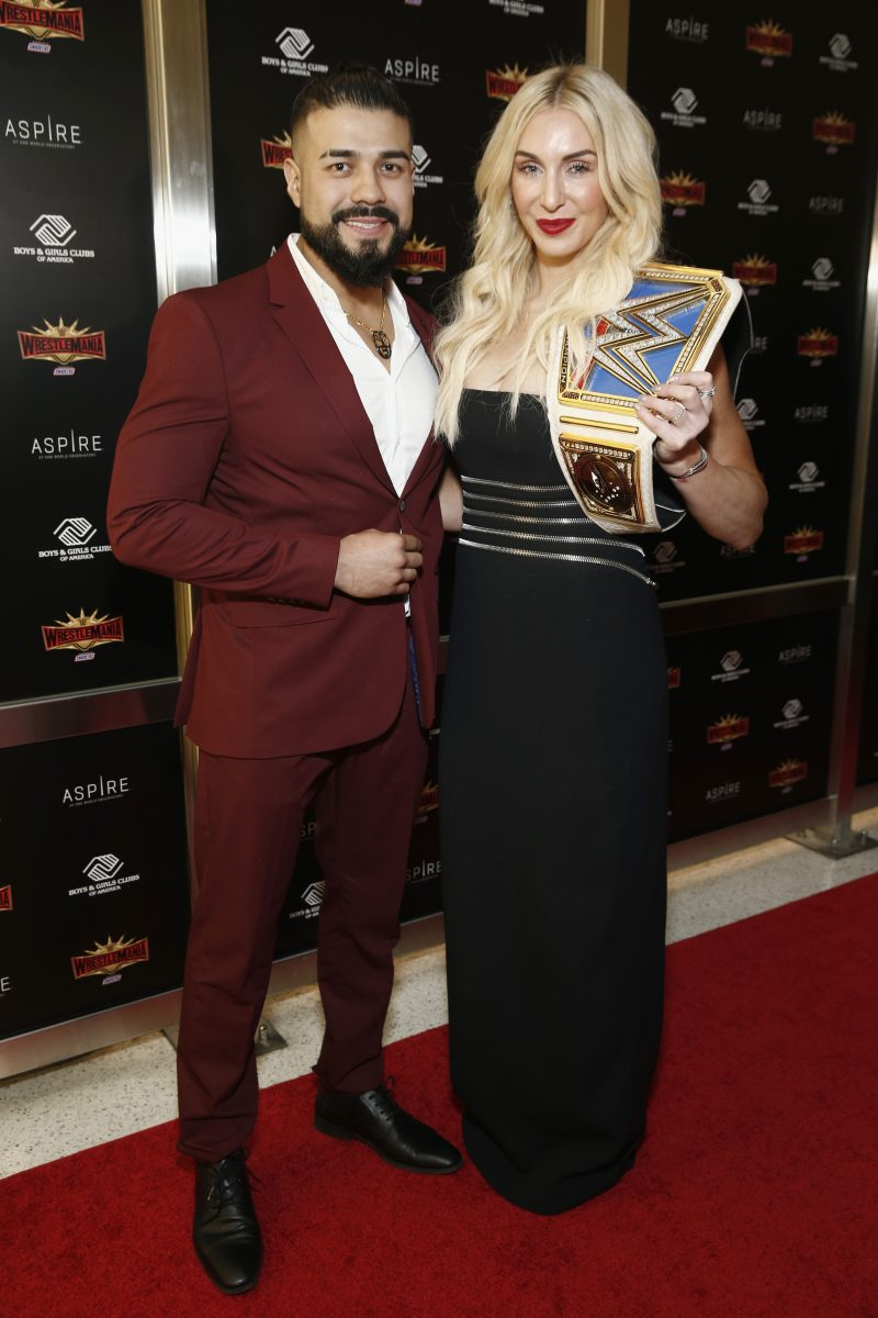 """WWE stars Andrade """"Cien"""" Almas and Charlotte Flair attend the 2019 Hall of Fame ceremony."""