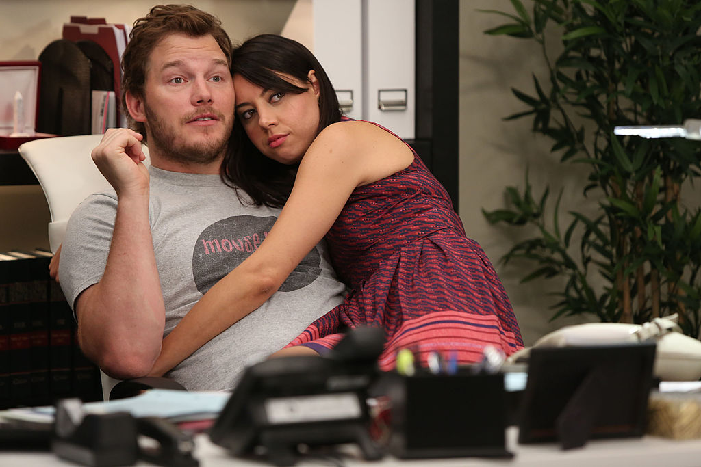 Chris Pratt as Andy, Aubrey Plaza as April Ludgate sit on the couch together. April has her arms around Andy.